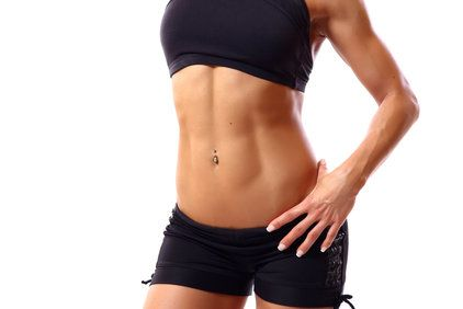 Woman holding hand over flat abdominal muscles