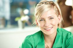 Smiling blond woman with reading lasses perched on head