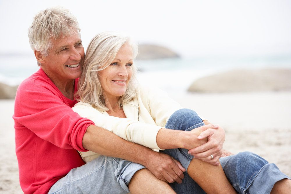 Older couple sitting on beach smiling