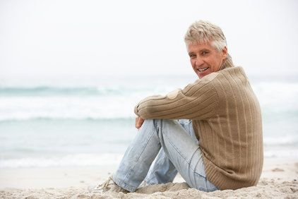 A man wearing a sweater sitting in the sand, facing the ocean.