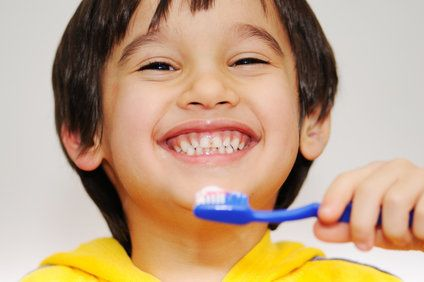 Child smiling holding toothbrush.
