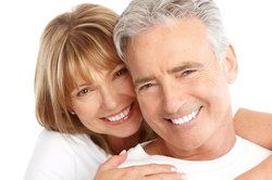 A man with dental implants smiles with his wife