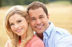 Attractive smiling couple posing in field