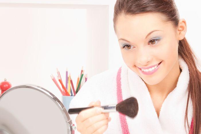 Girl in bathrobe applying makeup