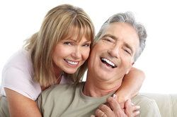 A man in a woman's embrace, both showing off their healthy smiles after gum disease treatment