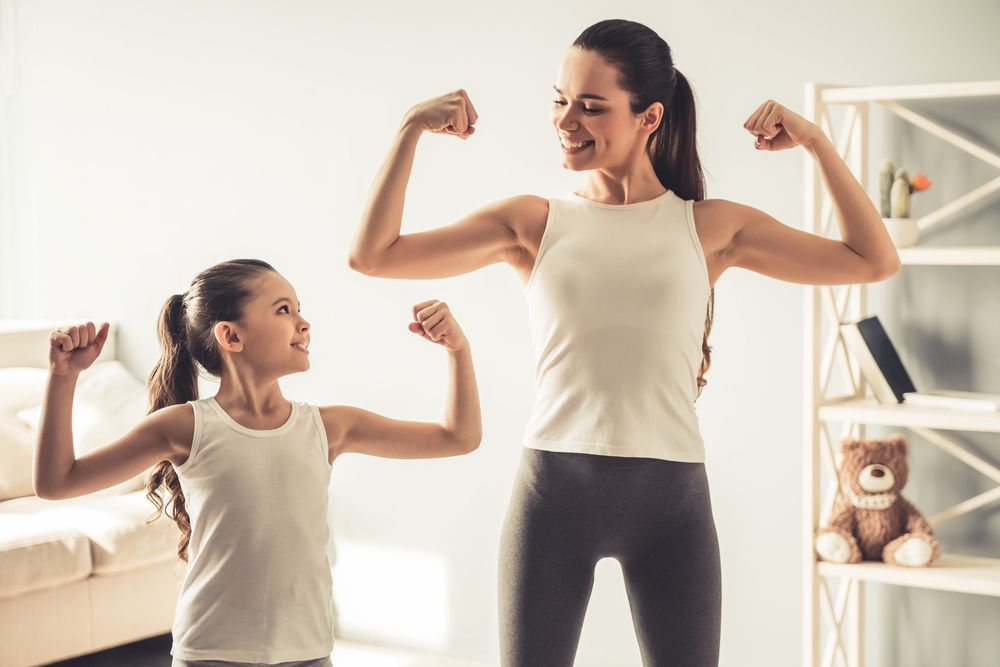 A fit mother after a mommy makeover showing off her muscles with her daughter