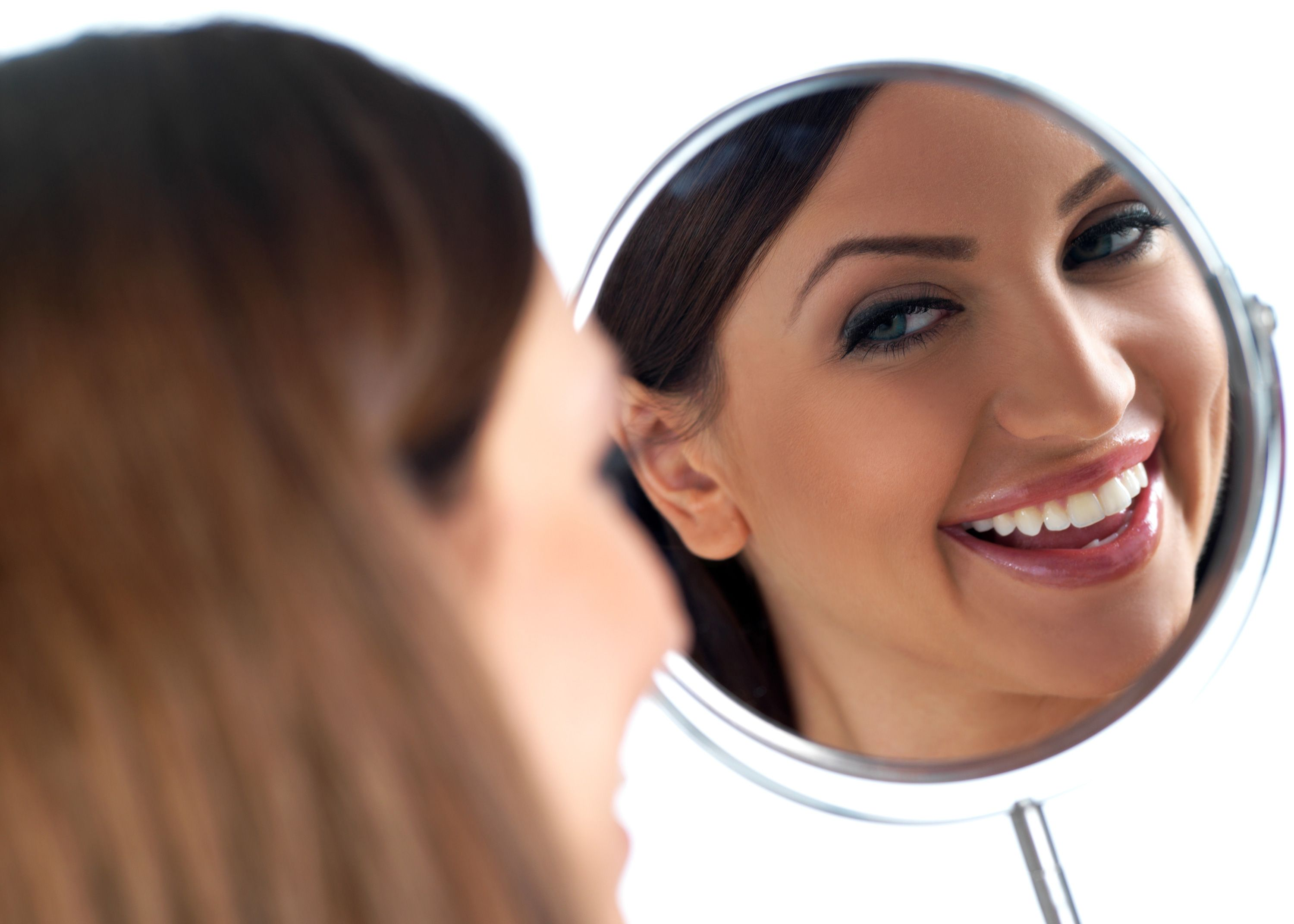 Young woman smiling in a handheld mirror