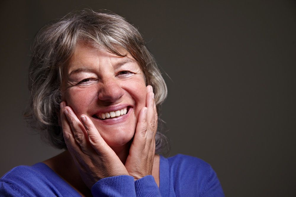A smiling woman with her hands on her face.