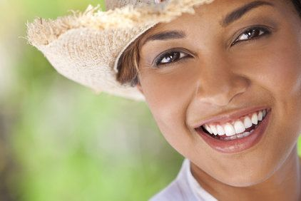 A woman in a hat, with a bright and beautiful smile