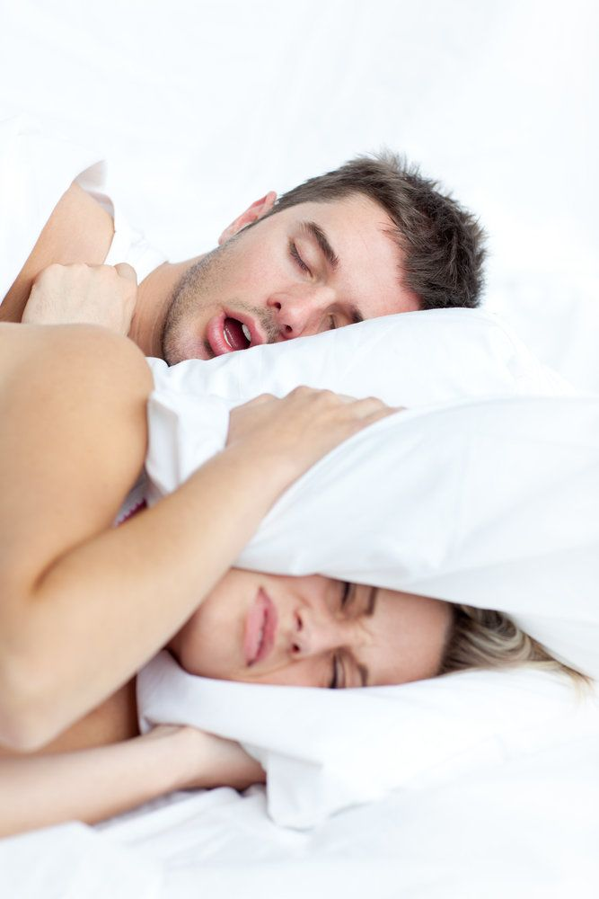 A woman covering her ears with a pillow while a man appears to be snoring in bed next to her