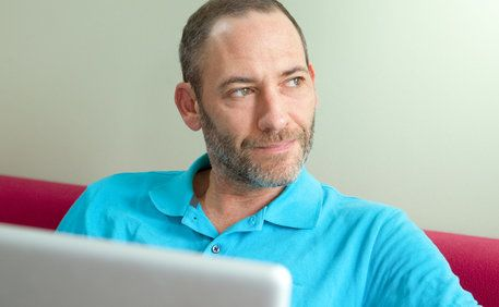 A middle-aged man looks perplexed while sitting in front of his computer.