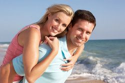 Couple piggybacking and posing for picture in front of surf