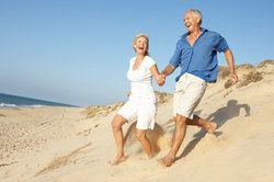 Older couple holding and hands and running through sand dunes