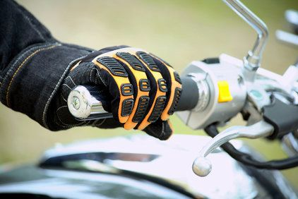 Close up of motorcyclist's gloved hand on throttle