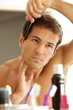 A man combs his full head of hair after while looking in the mirror