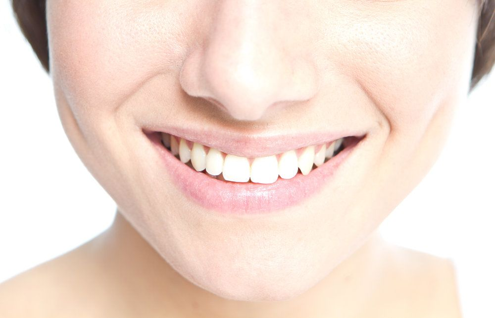 Close up of a woman's straight, uniform teeth after retainers-only treatment