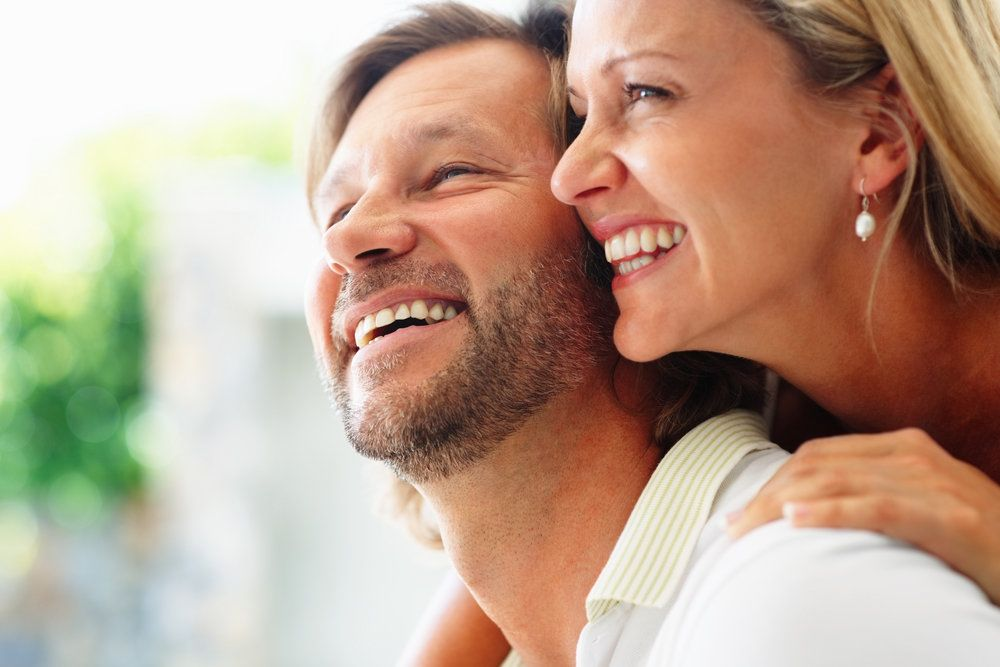 A middle-aged Caucasian couple smiles happily.