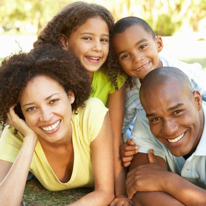 Smiling family lying on stomachs with two small children