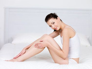 Woman with smooth legs sitting on bed