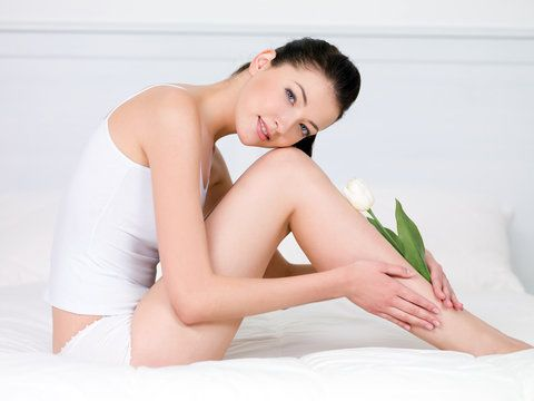 Beautiful young woman with white tulip on her attractive legs