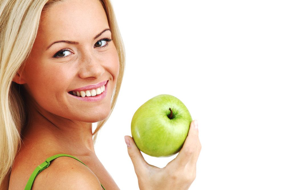 A post-bariatric patient holding up an apple