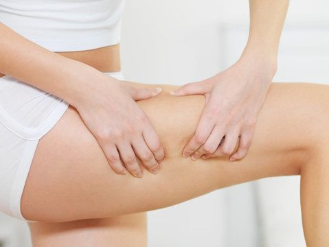 Woman squeezing the skin on her upper thigh