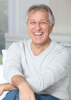 Smiling grey-haired man sitting on a couch