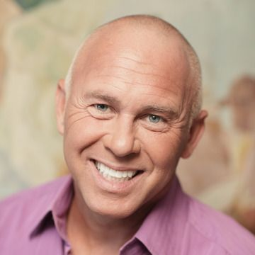 Smiling man in pink shirt with light blue eyes