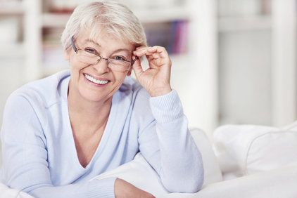 Mature woman with glasses on the sofa