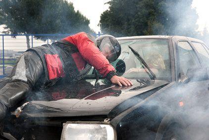 Victim of motorcycle crash laying on hood of car