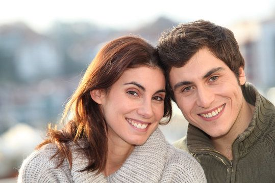 Smiling couple posing for picture with heads together