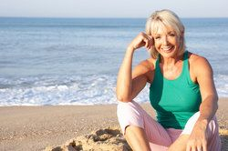 An older woman sitting on the beach with a healthy, white smile