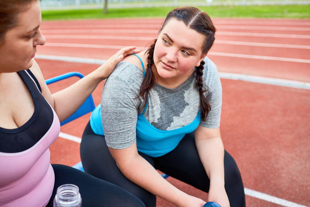young woman exercising at an outdoor track, receiving encouragement from a friend
