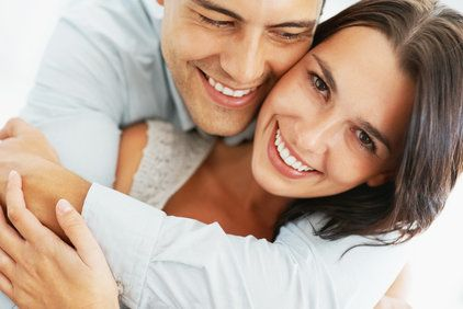 Smiling man hugging a brunette woman smiling.