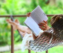 Woman in hammock reads a book.