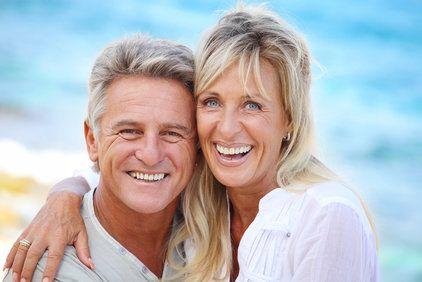 Smiling, middle-aged couple hugging and posing on beach