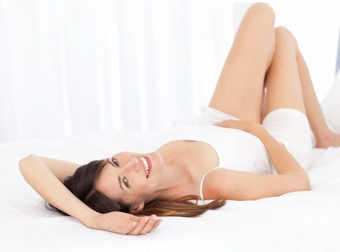Slim woman reclines, smiling at results of power assisted liposuction