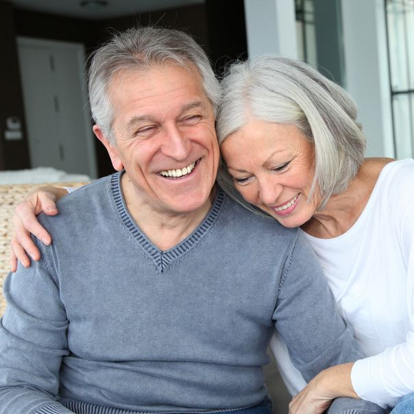 Older couple with complete, attractive smiles