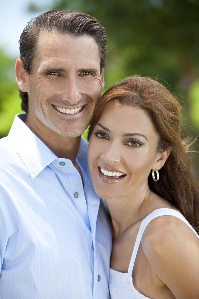Couple with white teeth posing outdoors.