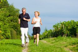 A Caucasian man and woman running through a wooded trail.