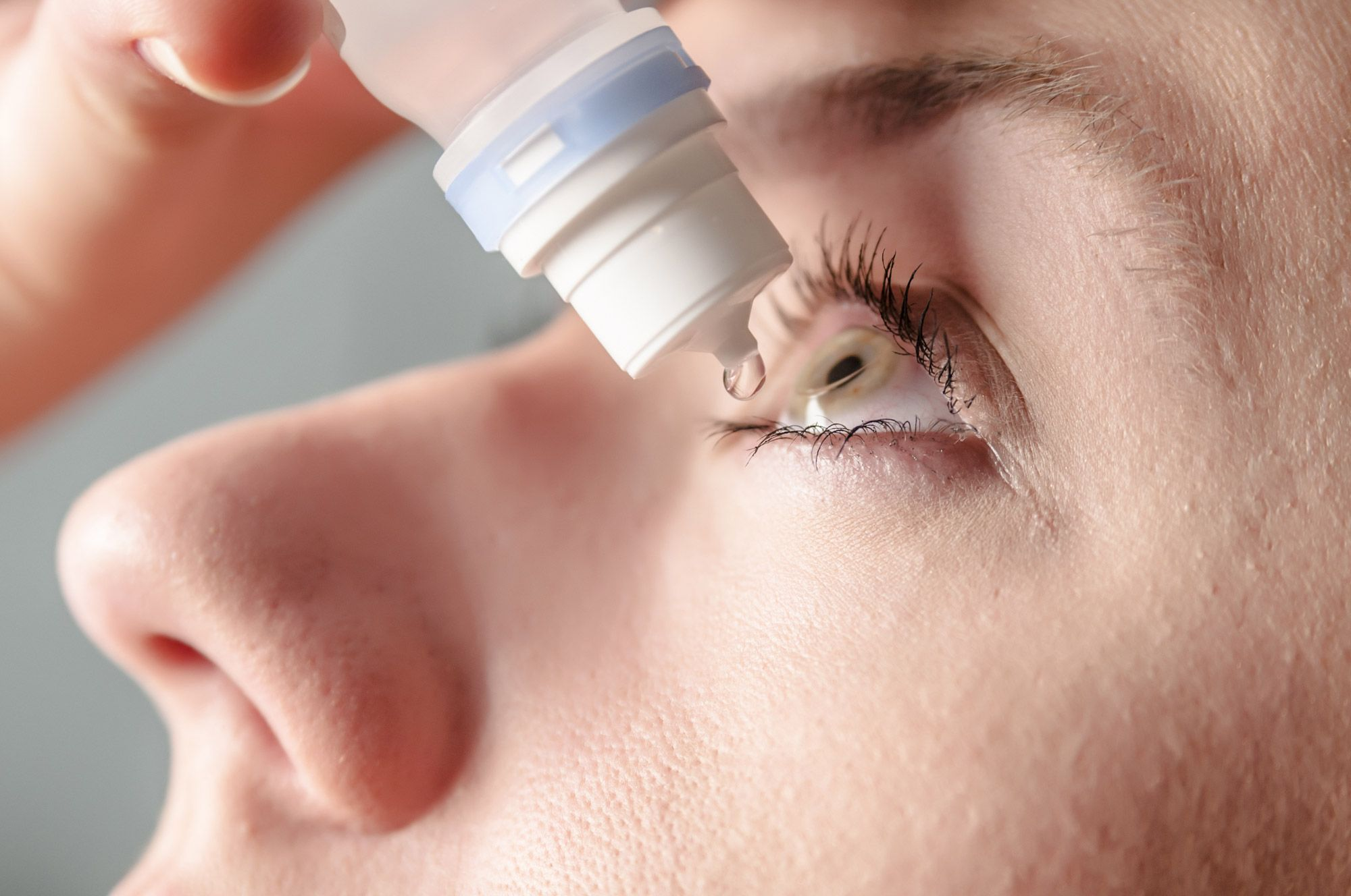 Woman using lubricating eye drops