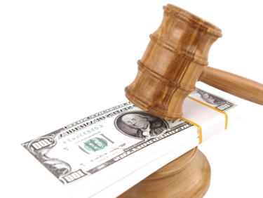 Wooden gavel resting on stack of hundred dollar bills