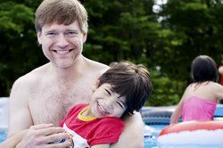 A father holding his son in the swimming pool