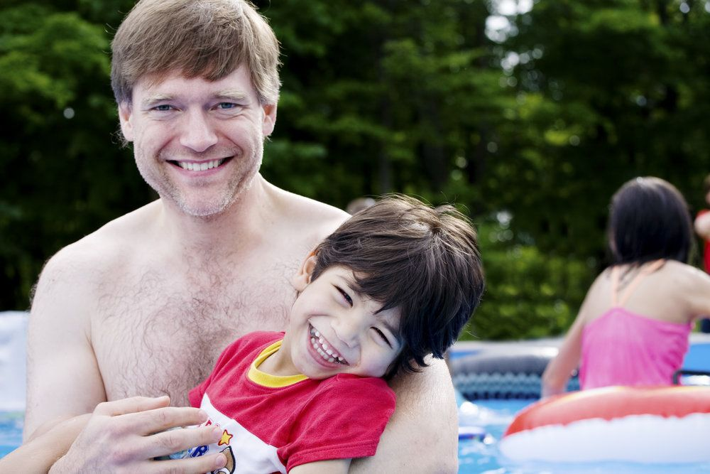 Male holding a child in a pool