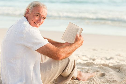 Older man sitting on beach