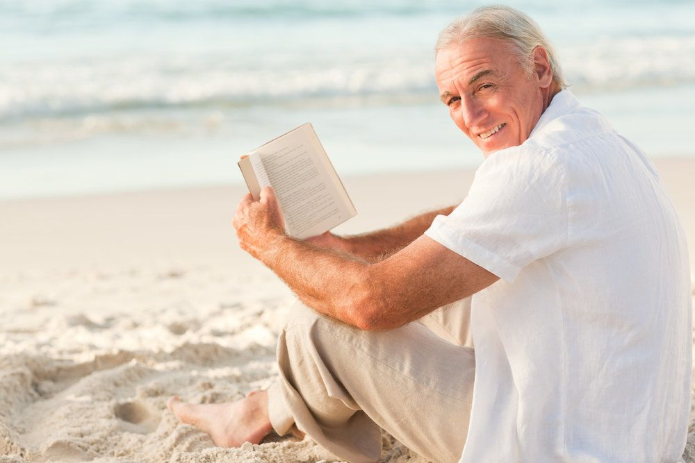 Older man reading on beach