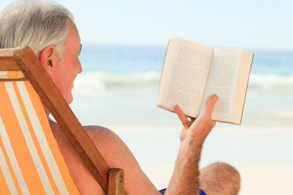 A gray-haired man reading a book at the beach.