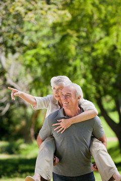 Smiling elderly couple riding bikes outside