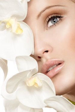 Beautiful woman with glowin skin holding orchids to face