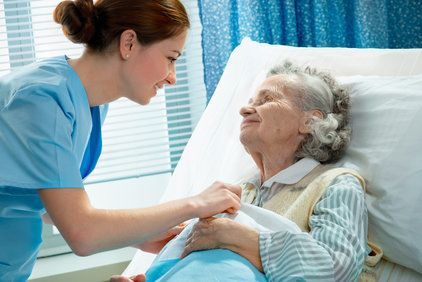 Nurse comforting elderly patient in hospital bed
